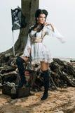 Piratenfrau, die nahe Schatztruhe steht Stockfotografie