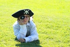 Piratenjunge, der auf Gras liegt Stockfoto
