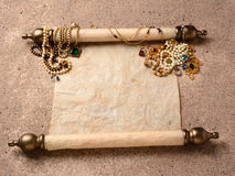 Pirates Booty. An ancient scroll laying on beach sand with jewelry scattered on it upper end. The scroll is blank ready for your treasure map or copy Royalty Free Stock Image