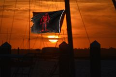 The sun sets with a pirate flag defiantly waving in the stiff breeze royalty free stock image