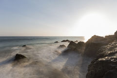 Pirates Cove Motion Blur Waves at Sunset in Malibu. Motion blur waves breaking over rocks with setting sun at Pirates Cove in Malibu, California Royalty Free Stock Image