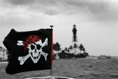 Pirates flag in black and red outdoor. Lighthouse at the background, Florida Royalty Free Stock Photos