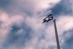 Pirates flag on mast against dramatic cloudy sky. Pirates flag on mast against dramatic, blue red cloudy sky. Malente, Germany royalty free stock image