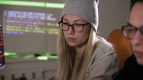 Pirates informatiques masculins et féminins travaillant sur des ordinateurs avec le code de données sur des écrans de visualisati banque de vidéos