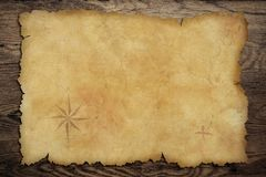 Pirates' old parchment treasure map on wood table. Pirates' old parchment treasure map on wood background royalty free illustration