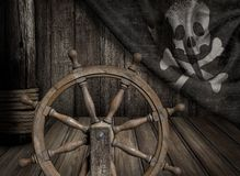 Pirates ship steering wheel with old jolly roger. Flag scene Royalty Free Stock Images