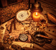 Pirates treasure background. Closeup on beautiful buccaneer treasure background, luxury pirates alcohol drink, cigars, compass, pearl beads, drawing map, piracy Stock Photography