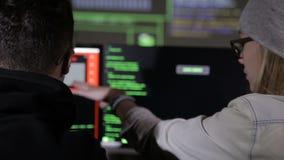 Pirati informatici nel lavorare scuro ai computer I pirati informatici codificano sullo schermo video d archivio