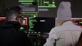 Pirati informatici nel lavorare scuro ai computer I pirati informatici codificano sullo schermo archivi video