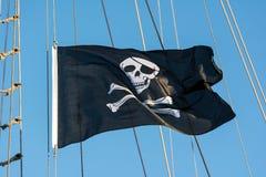 Piratkopiera flaggan med den mänskliga skallen Arkivfoto