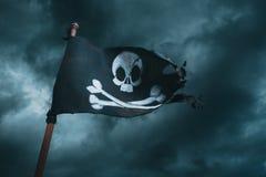 Piratkopiera flaggan som vinkar med vinden arkivbilder