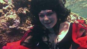 Piratkopierar den fria dykaren för ung flickamodellen som är undervattens- i röd dräkt av, i Röda havet arkivfilmer