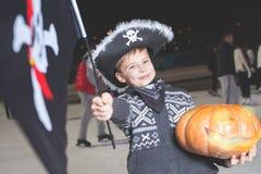 Piratkopierar den iklädda allhelgonaaftonen för pojke den utsmyckade dräkten med flaggan, pumpa Royaltyfria Bilder