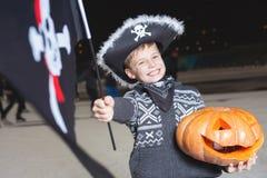 Piratkopierar den iklädda allhelgonaaftonen för stilig pojke maskeradkläderna med flaggan Royaltyfri Fotografi