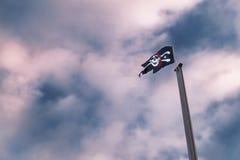 Piratkopierar flaggan på masten mot dramatisk molnig himmel royaltyfri bild