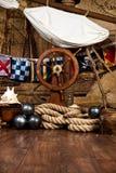 Piratkopierar skeppdäcket med den styrninghjulet och flaggan Arkivbild