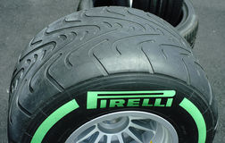 Pirelli F1 Race tyres. Pirelli Formula One race tyres on OZ race wheels on stands in the paddock. Lightly grooved Pirelli intermediate wet f1 race tyre Royalty Free Stock Photos