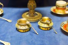 Pires da porcelana e um copo do chá em um fundo azul Fotografia de Stock