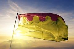 Pirkanmaa region of Finland flag textile cloth fabric waving on the top sunrise mist fog. Beautiful stock photo
