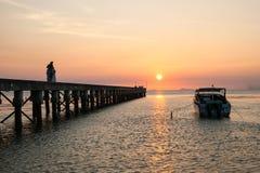 Pirlandskap på solnedgången, folk gå på en pir, lyckligt folk som går på havet och observerar en nedgång royaltyfria foton