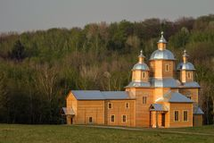 Wooden Orthodox church on the background of a hill covered with forests. On the sunset royalty free stock images