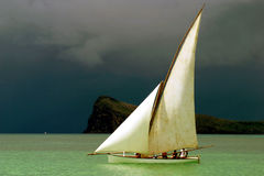 Pirogue naviguée blanche devant les nuages foncés Image stock