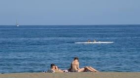 Pirogue ou canoë entrant en mer avec des personnes prenant un bain de soleil sur la plage banque de vidéos