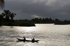 Pirogue under stormy sky. Dugout canoe on a silver lake of Pangalanes channel, Madagascar Stock Image