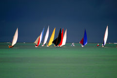 Pirogues on the horizon. In front of dark clouds in a regatta in the north of Mauritius Stock Photo