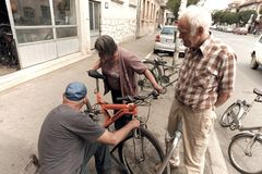 Mechanic Of Bicycles And Old Scooters In Pirot, Serbia. PIROT, SERBIA - JULY 27, 2017: a mechanic that repairs bicycles and old scooters is working on the stock photography