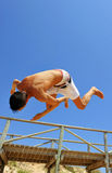 Pirouette of a teenager on the beach. A boy jumping with a blue sky in background Royalty Free Stock Images
