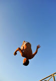 Pirouette of a teenager on the beach. A boy jumping with a blue sky in background Stock Photo