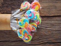 Piruleta colorida en el tablero de madera en el concepto de la diversión del ` s de los niños Imagen de archivo