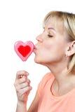 Piruleta en forma de corazón que se besa de la muchacha feliz Imagen de archivo libre de regalías