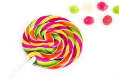 Piruleta redonda brillante dulce dulce del arco iris y muchas pequeñas piruletas coloridas en un fondo blanco Imagen de archivo