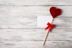 Piruleta roja del caramelo y nota en blanco sobre Grey Rustic Wood Background Imagen de archivo libre de regalías