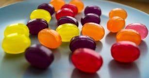 Piruletas coloreadas del caramelo presentadas en la placa Foto de archivo