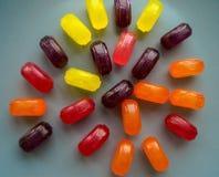 Piruletas coloreadas del caramelo presentadas en la placa Foto de archivo libre de regalías