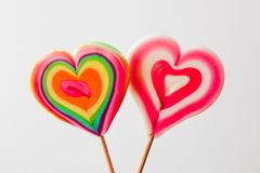 Piruletas en forma de corazón coloridas en fondo gris Imagen de archivo libre de regalías
