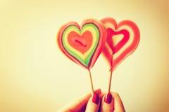 Piruletas en forma de corazón coloridas en mano de la mujer Imagen de archivo