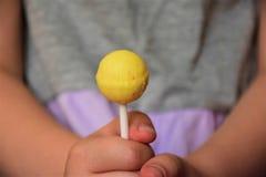 Pirulito nas mãos de uma criança Fotografia de Stock Royalty Free
