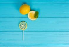 Pirulito pequeno como um limão na placa de madeira de turquesa perto do limão a Imagem de Stock