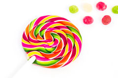 Pirulito redondo brilhante doce doce do arco-íris e muitos pirulitos pequenos coloridos em um fundo branco Imagem de Stock