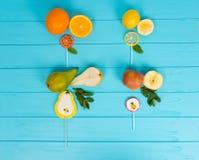 Pirulitos como uma pera, uma laranja, um limão e uma maçã na turquesa de madeira Foto de Stock Royalty Free