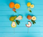 Pirulitos como uma pera, uma laranja, um limão e uma maçã na turquesa de madeira Foto de Stock