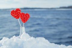Pirulitos dos corações na neve no fundo de ondas do mar Data romântica, declaração do amor, o dia de Valentim imagem de stock