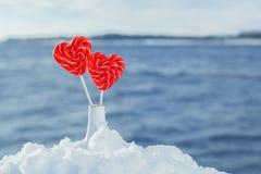 Pirulitos dos corações na neve no fundo de ondas do mar Data romântica, declaração do amor, o dia de Valentim fotografia de stock