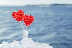 Pirulitos dos corações na neve no fundo de ondas do mar Data romântica, declaração do amor, o dia de Valentim imagens de stock