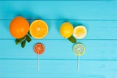 Pirulitos saborosos como uma laranja e um limão na boa de madeira de turquesa Fotografia de Stock