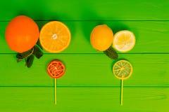 Pirulitos saborosos como uma laranja e um limão na placa verde de madeira n Foto de Stock